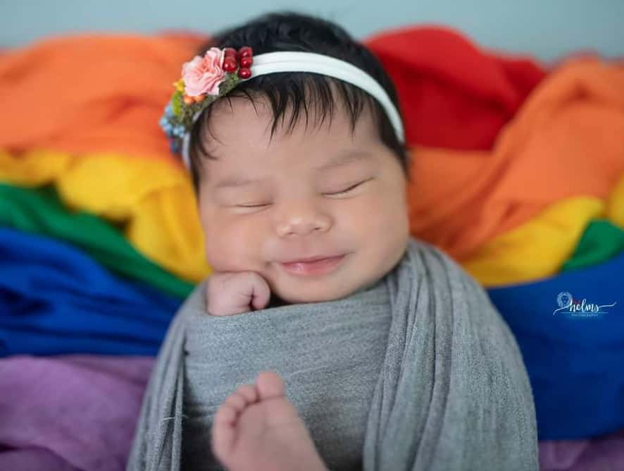 baby wrapped in rainbow blanket - testimonial for Larua L.