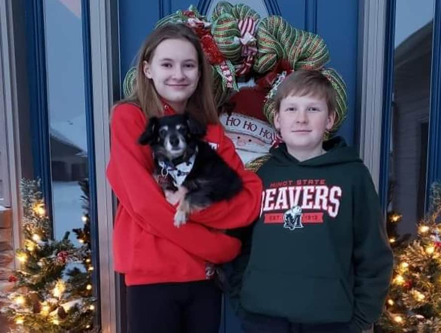 two teens standing in front of a dog holding dog. - testimonial for Melinda S.